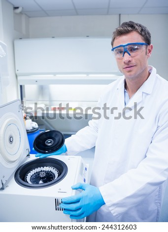 Chemist wearing safety glasses and using a centrifuge in lab - stock photo