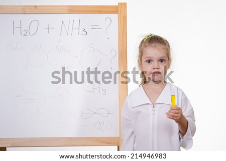 Chemist with test tube at the blackboard - stock photo