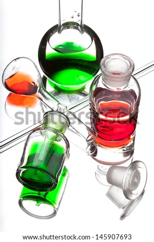 Chemistry laboratory glassware with colour liquids in them on white background  - stock photo