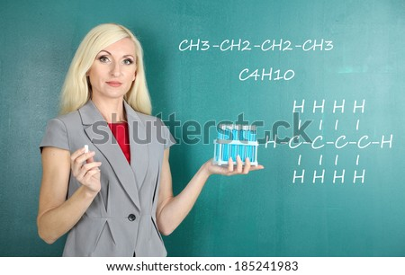 Chemistry teacher explaining formula written on blackboard to her pupils - stock photo