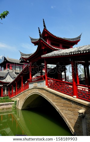 CHENGDU, CHINA:  A handsome bridge with flying eave roofs and covered arcades spans a waterway at the Long Tan Water Town - stock photo