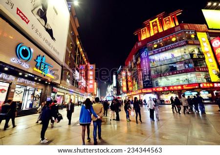Chengdu, China - October 26, 2013: People can seen walking and shopping around the Chunxi road in Chengdu,China at night - stock photo