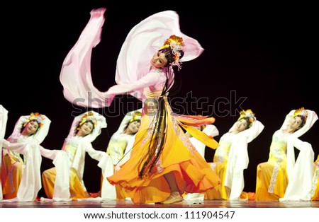 CHENGDU - OCT 17: Chinese national dancers perform folk dance on stage at JINCHENG theater on Oct 17, 2011 in Chengdu, China. - stock photo