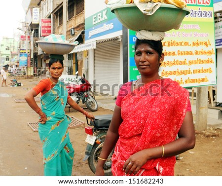 CHENNAI/INDIA - AUG 10. Two unidentified indian women carrying a heavy baskets on theirs heads on August 10, 2013 in a street of Chennai, Tamil Nadu, India. There are a lot of women who work hard.  - stock photo