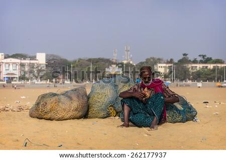 CHENNAI, INDIA - FEBRUARY 10, 2013: Unidentified old fisherman smoking on Marina beach in Chennai, Tamil Nadu, India - stock photo
