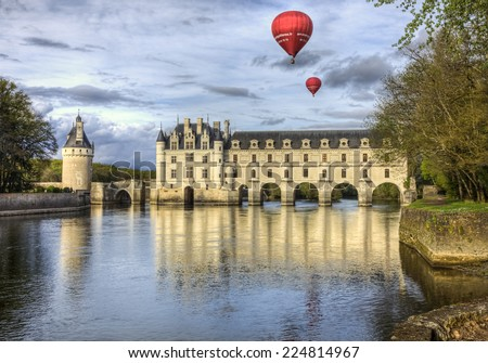 CHENONCEAUX, FRANCE-APRIL 6: Two red hot air balloons fly above the Chenonceau Castle spanning the river Cher in Chenonceaux ,France on April 6, 2014. This is a famous castle located on Loire Valley. - stock photo