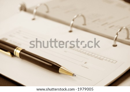 cheque with notebook for business concept - stock photo