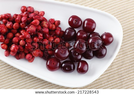 Cherries and cherry stones (pits) on a plate. - stock photo