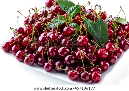 cherries berries on square plate close-up on white background   - stock photo