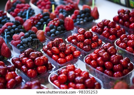 Cherries grouped together in mini clear containers; containers of mixed berries surround the containers of cherries. - stock photo