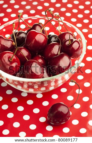 Cherries in a glass bowl on polka dot background - stock photo