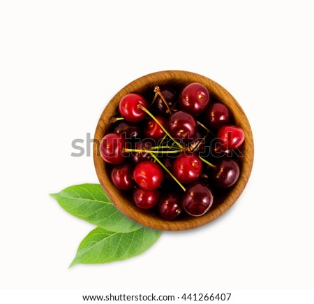 Cherries in a wooden bowl with with leaves. Top view. Ripe and tasty cherries isolated on white background. Cherries in a bowl. - stock photo