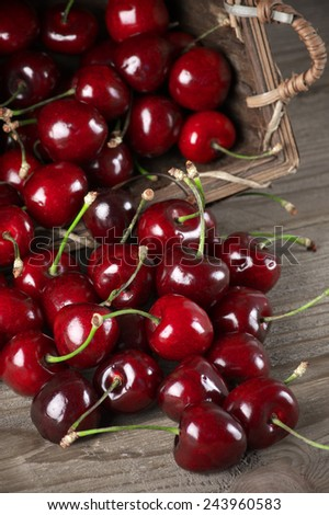Cherries spilled from basket on wooden background. - stock photo