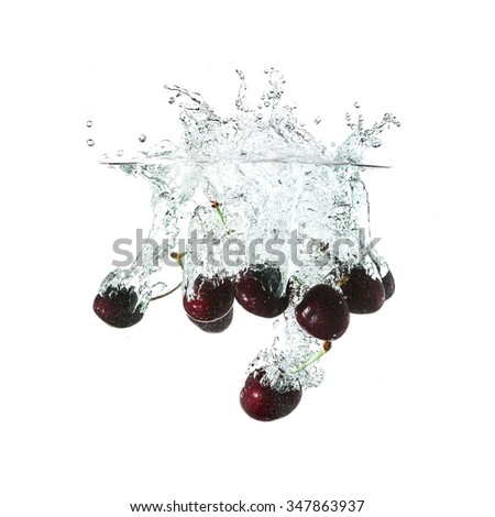 Cherries splash on water, isolated on white background. Use for fresh drinks advertising. - stock photo