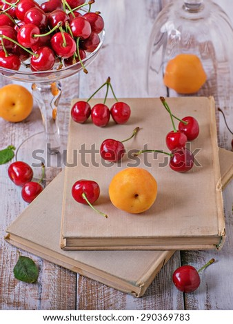 Cherry, apricots and old books on a wooden table - stock photo