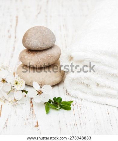 Cherry blossom, massage stone and towels on a wooden background - stock photo