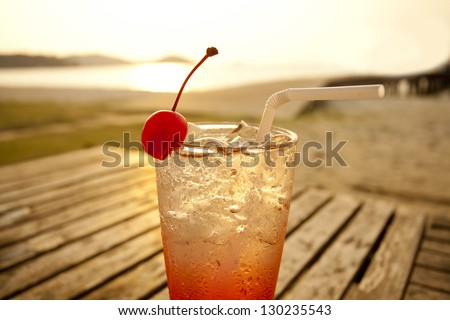 cherry cocktail by the sea, red spirit drink in tall glass decorated cherry by the sea - stock photo