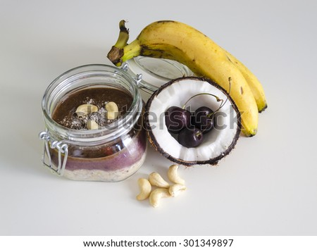 Cherry coconut banana overnight oats with cracked open coco,banana,cashews mixed with chia seeds and cherry cream in a mason jar,a tropical meal on white background. Healthy fitness breakfast oatmeal. - stock photo