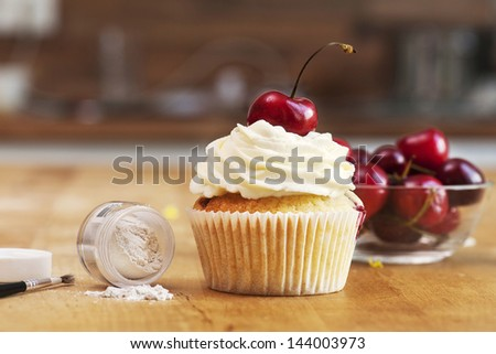 Cherry Jam Cupcake Shot on table in studio with organic background, a brush and food glitter as icing as a kind of making of - stock photo