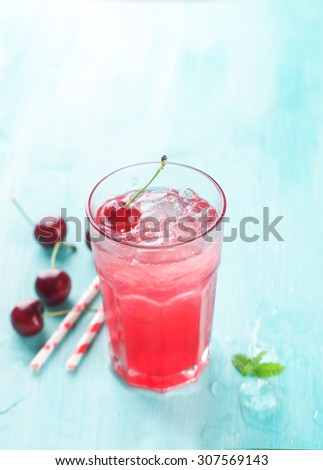 Cherry lemonade with ice cube, selective focus - stock photo