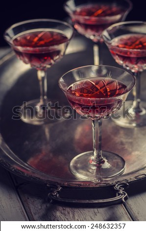 Cherry liqueur in vintage crystal glasses over dark background - stock photo