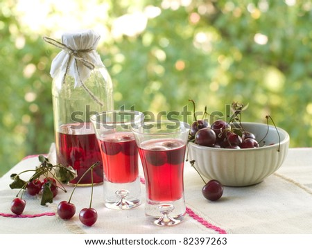 Cherry liquor in glass on natural background. Selective focus - stock photo