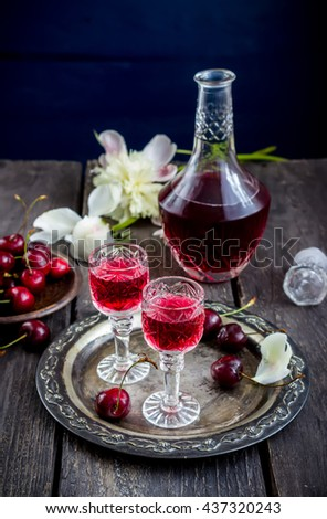 Cherry  liquor in glasses  and vintage bottle on metal tray. Wooden background, selective focus. - stock photo