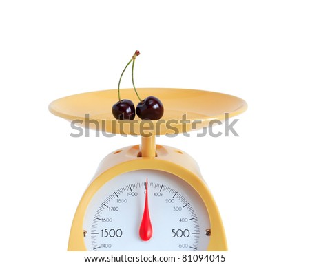 Cherry lying on yellow kitchen scale. Isolated on white background with clipping path - stock photo