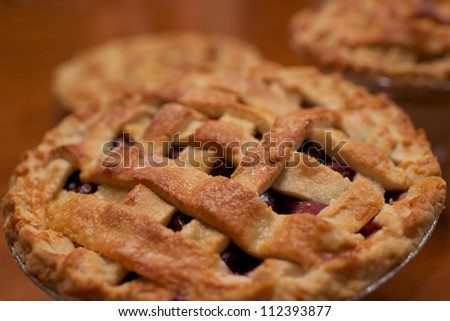 Cherry pie with two more pies in the background. - stock photo
