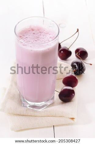 Cherry smoothie in glass on wooden table - stock photo