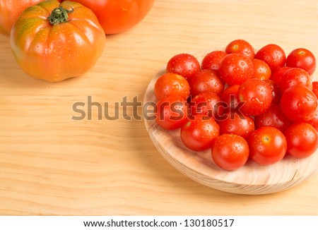 Cherry tomatoes against the background of bigger types - stock photo