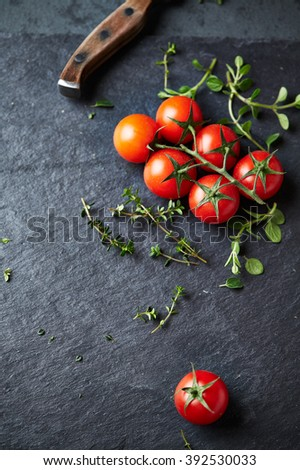 Cherry tomatoes and herbs on a black slate  - stock photo