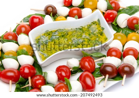 Cherry tomatoes and mozzarella on skewers and a vinaigrette sauce with basil, isolated on white - stock photo