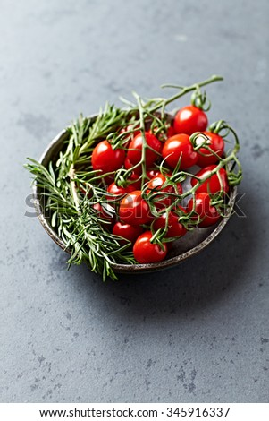 Cherry tomatoes and rosemary in a ceramic bowl - stock photo