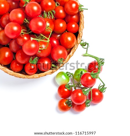 Cherry tomatoes in a basket and twig, isolated on white - stock photo