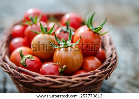 Cherry tomatoes in a small basket on an old wooden surface, space for text. Natural light, close up, selective focus. - stock photo