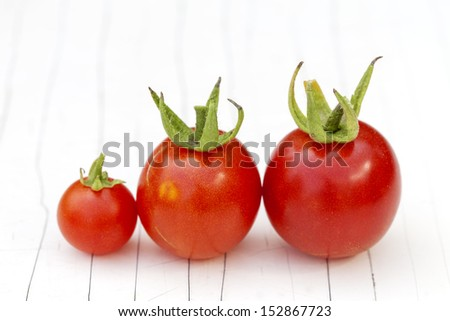 Cherry tomatoes line up on the white cracked background, close up. - stock photo