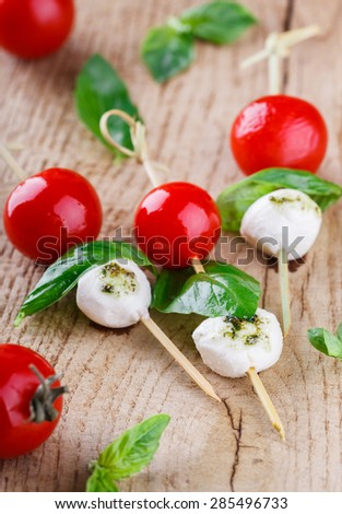 Cherry tomatoes,mozzarella and Basil on skewers. Appetizer,Caprese. - stock photo