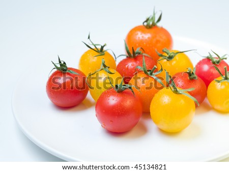 cherry tomatoes on a white plate - stock photo