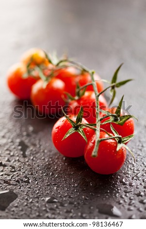 Cherry Tomatoes on Black Stone Surface - stock photo