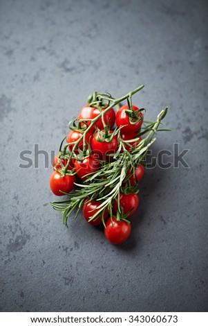 Cherry tomatoes on the vine and rosemary - stock photo