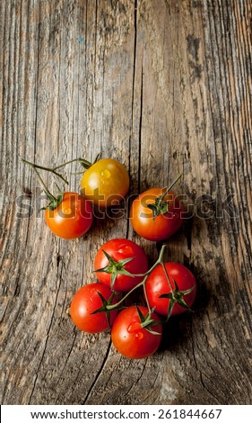 Cherry tomatoes on vintage wood table - rural still life from above. Fresh harvest from garden. Background layout with free text space. - stock photo