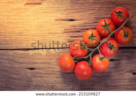 Cherry tomatoes on wood - stock photo