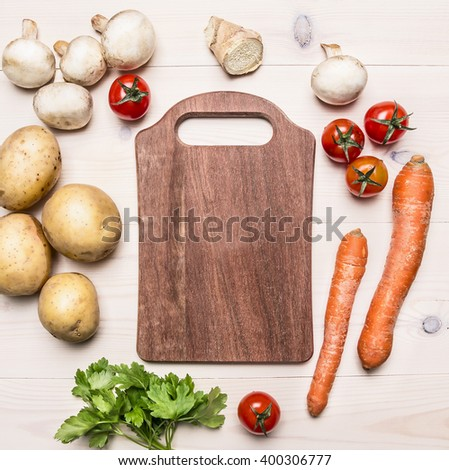 cherry tomatoes, potatoes, carrots, parsley and mushrooms laid out around a cutting board place for text,frame on wooden rustic background top view - stock photo