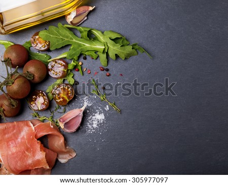 Cherry tomatoes, prosciutto, arugula and spices on black board, top view - stock photo