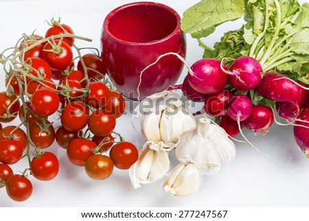 Cherry tomatoes, radishes and garlic in a studio shot - stock photo