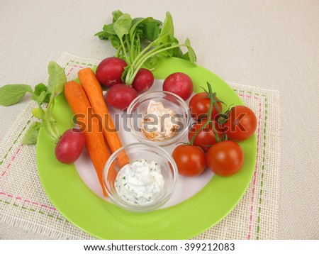 Cherry tomatoes, red radishes, carrots and fresh cheese dipping sauce - stock photo