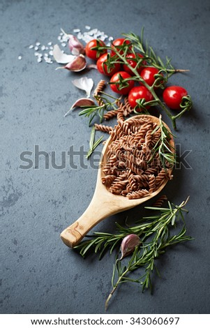 Cherry tomatoes, spices and whole grain spelt pasta - stock photo