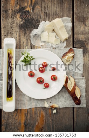 Cherry tomatoes with basil on a white plate, next to a half eaten bread bun, hard yellow cheese and olive oil with balsamic vinegar, on a wooden table. Copy space. - stock photo