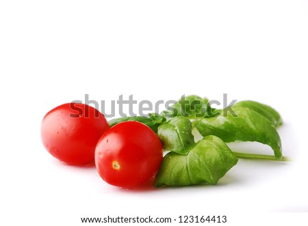 Cherry tomatoes with basil on the white background - stock photo